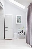 Retro-Kühlschrank in weißer Küche neben einem Servierwagen mit Bar