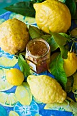 A jar of lemon jam and fresh lemons