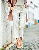 Frau in gestreifter 7/8-Hose, beigefarbener Seidenbluse, rosefarbenem Mantel und Wedges