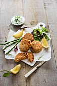 Salmon fishcakes with cucumber, yoghurt and chive dip, fresh salad, asparagus and lemon wedges