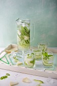 A jug and glasses of refreshing cucumber and melon water with fresh mint for summer.