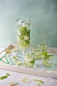 Gurken-Melonen-Wasser mit frischer Minze in Gläsern und Glaskrug