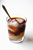 Iced coffee in a glass with ice cubes and milk