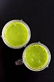 Two green smoothies with spinach in a blender jar
