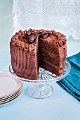 Chocolate layer cake with slice taken out on glass cake stand