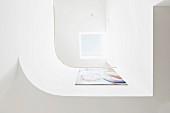 Blick auf gerundete, weiße Brüstung mit Gemälde und hellem Oberlichtfenster