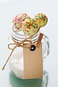 Cake pops with a white chocolate glaze and sugar beads