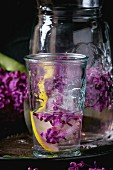 Glass and pitcher of lilac lemonade water with lemon, ice cubes with lilac flowers and lilac branch