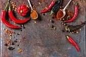 Chilistilleben: Verschiedene frische Chilischoten, Chilipulver, Chiliflocken und Piment