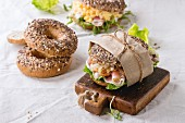 Whole Grain bagels with scrambled eggs, pea sprout, fried onions and prosciutto ham