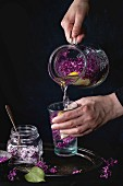 Femail hands poured from jug to glass lilac lemonade with lemon