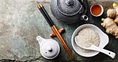 Asiatisches Stillleben mit Teekanne, Ess-Stäbchen, Ingwer und Reis