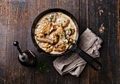 Roasted chicken with creamy garlic sauce in cast iron frying pan on dark wooden background