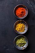 Paprikapulver, Curry und Matcha-Teepulver in Schälchen vor dunklem Hintergrund