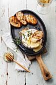 Gebackener Camembert mit geröstetem Brot in gusseiserner Pfanne
