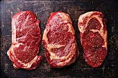 Three cuts of Raw fresh meat Steaks and seasonings on dark background
