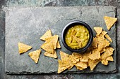 Fresh guacamole dip with nachos chips on stone slate background