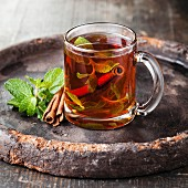 Mint tea with cinnamon on dark background