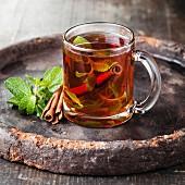 Mint tea with cinnamon on dark background