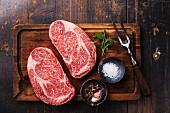Zwei rohe Black Angus Ribeye Steaks mit Gewürzen und Fleischgabel auf Holzbrett