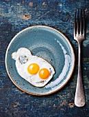 Spiegeleier auf blauem Teller fürs traditionelle Frühstück (Aufsicht)