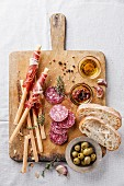 Bread sticks with ham and salami on wooden background