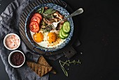 Breakfast set. Pan of fried eggs with bacon, fresh tomato, cucumber, sage and bread on dark serving board