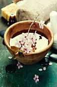 Aromaöl in Holzschale mit Kirschblütenzweig, dahinter Spa-Utensilien