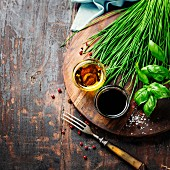 Essig, Öl, frische Kräuter und Gewürze auf Holzbrett