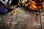 Kräutertee mit Wildblumen in Teedose und aufgebrüht in Glastasse