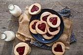 Linzer Plätzchen mit Herzmotiv und Erdbeermarmelade, daneben Milchflaschen
