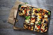 Selbstgemachte Pizza mit gebratenem Gemüse, Oliven und Basilikum auf Backblech