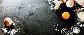 Backzutaten: Aufgeschlagene Eier, Zucker und Mehl auf dunklem Untergrund