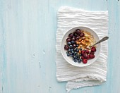 Healthy breakfast set. Bowl of oat porridge with fresh berries, almond and honey over white napkin