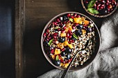 A bowl of coconut quinoa porridge, pomegranate seeds and sliced apricots