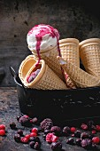 Homemade vanilla ice cream in wafer cones and empty waffer cones