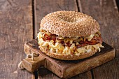 Bagel with bacon, scrambled eggs and fried onion on small wooden chopping board