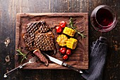 Sliced Medium rare grilled Steak Ribeye Black Angus with corn and cherry tomatoes on serving board block
