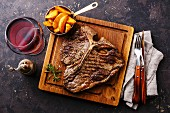 Medium gegrilltes T-Bone Steak mit Potato Wedges und Wein auf Servierbrett