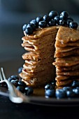 Stack of Apple spelt pancakes topped with maple syrup and fresh blueberries