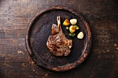 Ribeye Steak on bone with vegetables on stone plate on wooden background