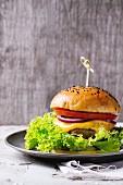 Hausgemachter Hamburger mit schwarzem Sesam auf Zinnteller