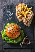 Fresh homemade hamburger with black sesame seeds and french fries potatoes in backing paper