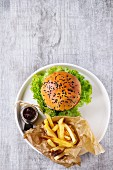 Fresh homemade burger with black sesame seeds in white plate with fried potatoes