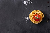 Top view on dry pasta and fresh cherry tomato served with sea salt on dark grey slate background