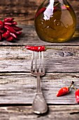 Red hot chili pepper on vintage fork over old wooden background