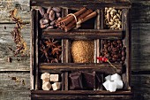 Coffee and cocoa beans, sugar cubes, dark chocolate, cinnamon and anise over wooden background