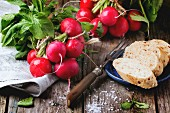 Fresh wet radishes with vintage fork, sea salt and bread over old wooden table