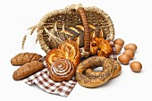 Assortment of baked bread with wheat in basket isolated on white background