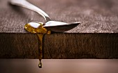 Honey dripping off spoon on rustic wood surface